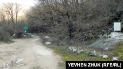 Шлагбаум на дороге к Варнутскому мосту, справа – памятная табличка
