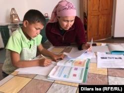 Мама с сыном делают домашние задания, которые мальчик получает по почте, село Амангельды, Туркестанская область.