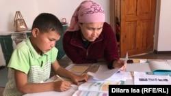 Жительница Туркестанской области учит уроки с сыном. Иллюстративное фото.