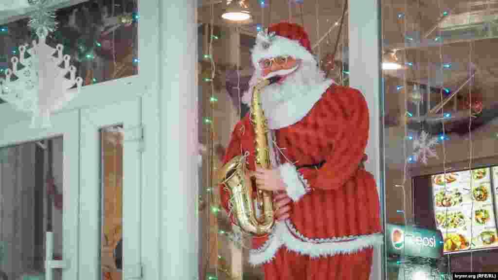 Ростовая кукла Санта Клауса, играющего на саксофоне, у входа в одно из заведений общепита на набережной Ялты