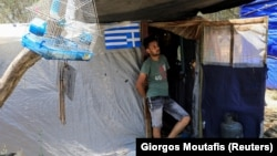 Мигрант пред бегалски камп на грчкиот остров Самос.