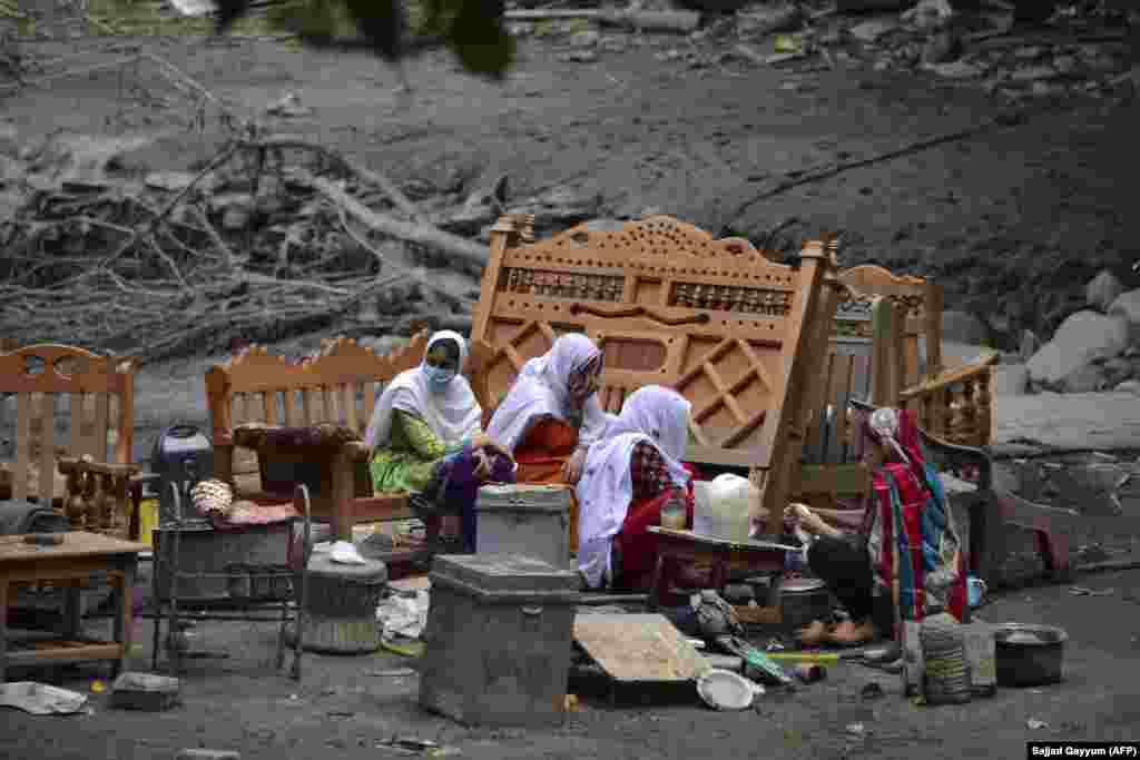 A family gathers around their belongings outside their damaged house following heavy monsoon rains in Neelum Valley, near the Line of Control in Pakistan-controlled Kashmir. In Pakistan-administered Kashmir, officials said at least 23 people were killed after heavy rain triggered flash floods and damaged more than 120 houses and 30 shops. (AFP/Sajjad Qayyum)