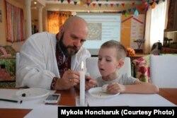 Мікола Ганчарук праводзіць майстар-клясу па размалёўваньні велікодных яек у цэнтры для анкахворых дзяцей