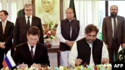 Pakistani Oil Minister Shahid Khaqan Abbasi (R) and Russian Energy Minister Aleksandr Novak sign an agreement on the North-South gas pipeline project as Pakistani Prime Minister Nawaz Sharif looks on during a ceremony in October 2015.