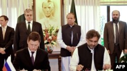 Russian Energy Minister Aleksandr Novak (L) and Pakistani Petroleum Minister Shahid Khaqan Abbasi sign an agreement of the North-South gas pipeline project as Pakistani Prime Minister Nawaz Sharif looks on during a ceremony in Islamabad on October 16.