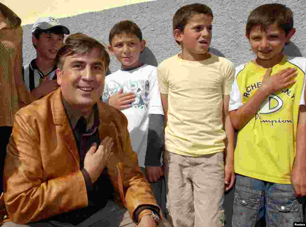 Georgian President Mikheil Saakashvili sings the national anthem with children in Kodori Gorge, a section of the rebel Georgian region of Abkhazia controlled at the time by Georgian forces (September 27, 2006).