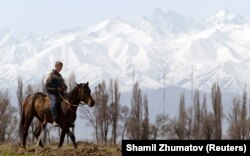 A Kyrgyz horseman rides at the foothills of Ala-Too mountains some 50 km (31 miles) east of the country's capital of Bishkek in Kyrgystan April 2, 2005