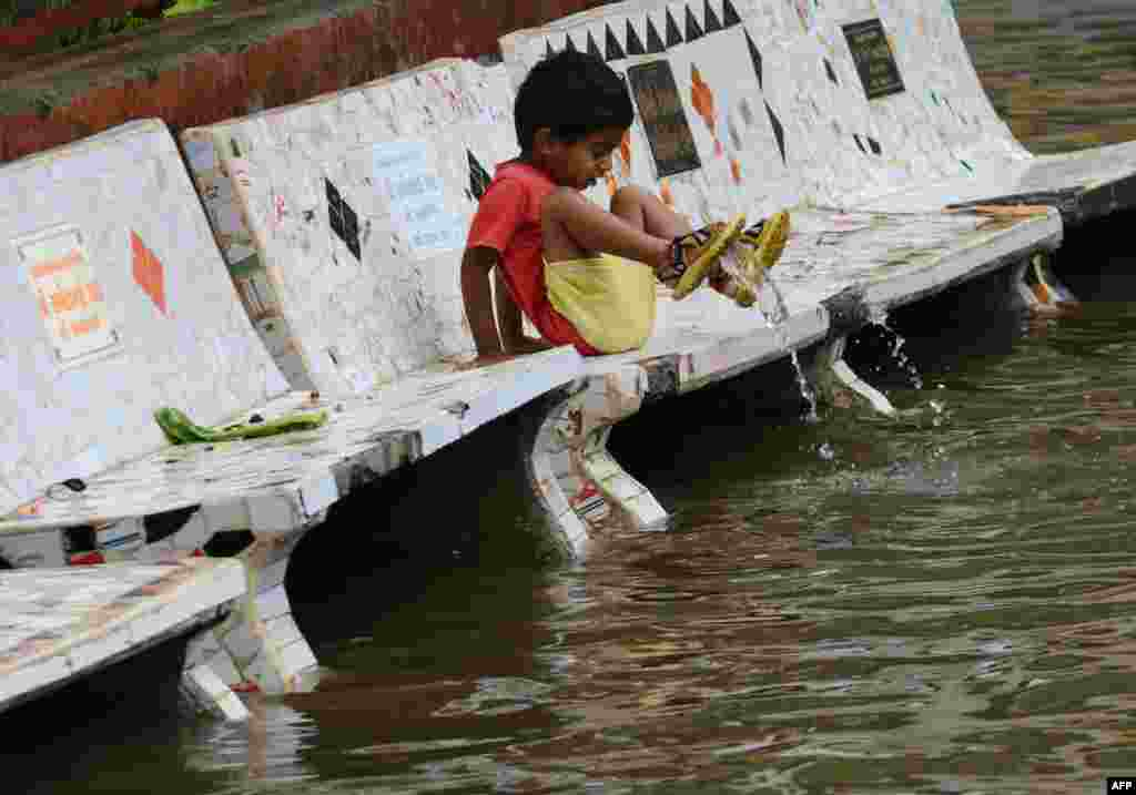 A child reacts to floodwaters in Ahmedabad after heavy rains lashed Gujarat state. (AFP/Sam Panthaky)