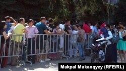 """Люди стоят в очереди на подачу документов для получения квартир по госпрограмме """"Доступное жилье - 2020"""". Алматы, 10 июля 2013 года."""
