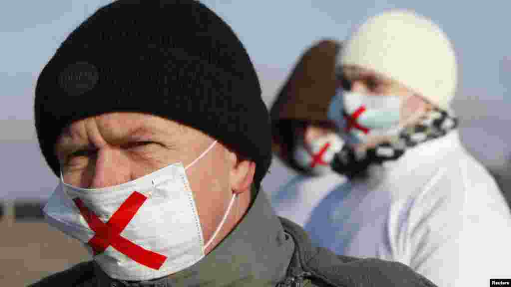 Demonstrators wearing masks take part in the protest against recent parliamentary election results in the southern Russian city of Stavropol.