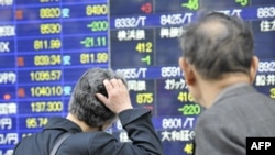 Pedestrians look at a share prices board in Tokyo on April 28 after share prices fell amid fears over the swine-flu outbreak.