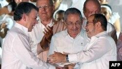 Presidenti i Kolumbisë, Juan Manuel Santos (majtas) dhe lideri i FARC-ut, Rodrigo Londono, duke u përshëndetur pas nënshkrimit të marrëveshjes së parë; në mes është presidenti i Kubës, Raul Castro