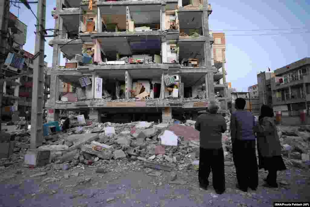People look at destroyed buildings in Sarpol-e Zahab.