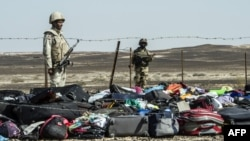 Egyptian Army soldiers stand guard next to the luggage and belongings of passengers from the Russian airliner piled up at the site of the crash in Wadi el-Zolmat, a mountainous area on the Sinai Peninsula.