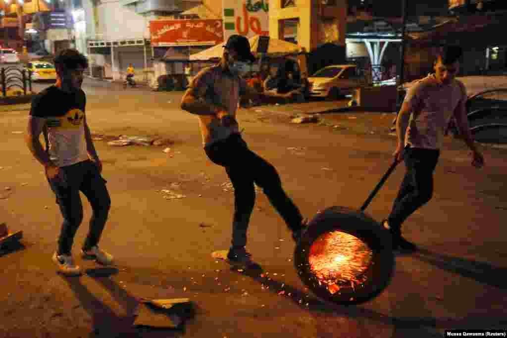 Egy égő gumiabroncsot gurítanak végig az utcán Hebron városában. Az indulatokat a Ramadán ünnep alatti korlátozások váltották ki.