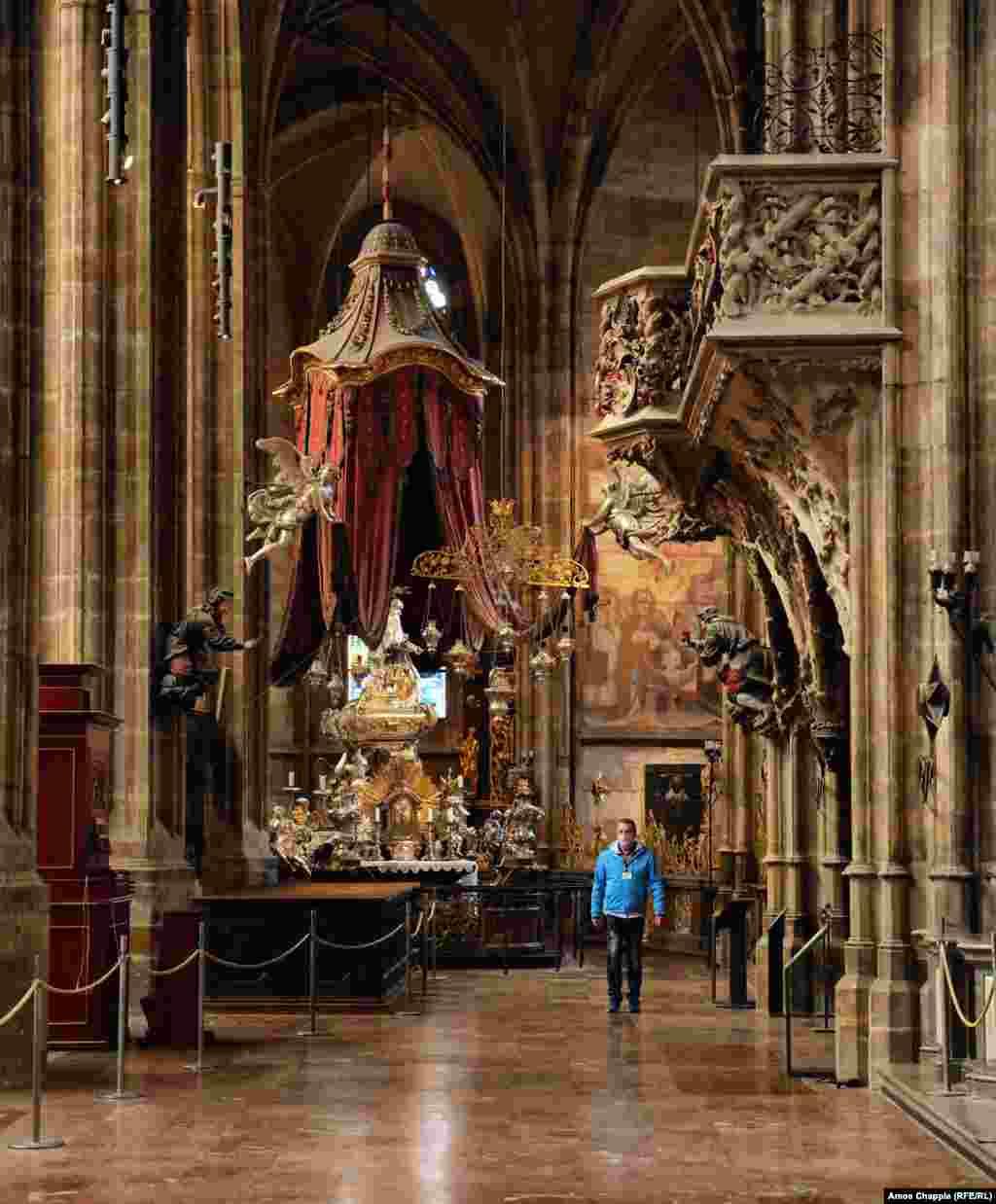 Рабочий идет по почти пустому собору Святого Вита, архитектурному центру Пражского града