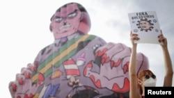"""Një protestuese duke mbajtur një baner me mbishkrimin """"Virusi Bolsonaro, jashtë""""."""