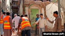 Pakistani volunteers collect debris from a demolished Ahmadi mosque in the eastern city of Sialkot on May 24.
