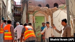 Pakistani volunteers collect debris from a demolished Ahmadi mosque that was demolished by an angry mob on May 24 in the eastern Pakistani city of Sialkot