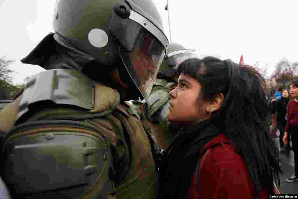 A demonstrator stares down a riot policeman during a protest marking the country's 1973 military coup in Santiago. (Reuters/Carlos Vera)