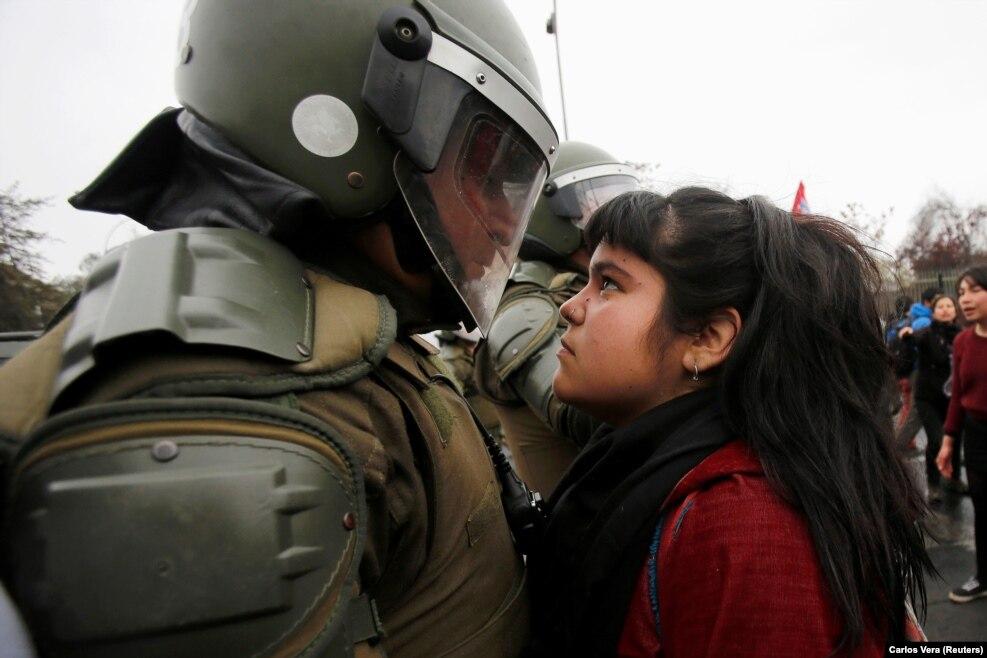 مراسمی به یاد قربانیان کودتای شیلی در ۱۱ سپتامبر ۱۹۷۳ عکس کودکی در میان معترضان، چشم در چشم مامور امنیتی، دنیایی را مجذوب خود کرد.