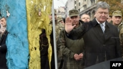 Ukrainian President Petro Poroshenko pays his respect to a Ukrainian flag found close to the remains of fallen soldiers in eastern Ukraine. Local elections this week are being seen as an important barometer of how Ukrainians think his administration is handling the country's myriad problems.