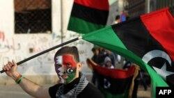 Прихильник повстанців на демонстрації за міжнародну операцію в Бенгазі з повстанським прапором, який мала Лівія до перевороту Каддафі 1969 року. На другій половині його обличчя зображений також прапор Катару – єдиної наразі арабської держави, яка надала д
