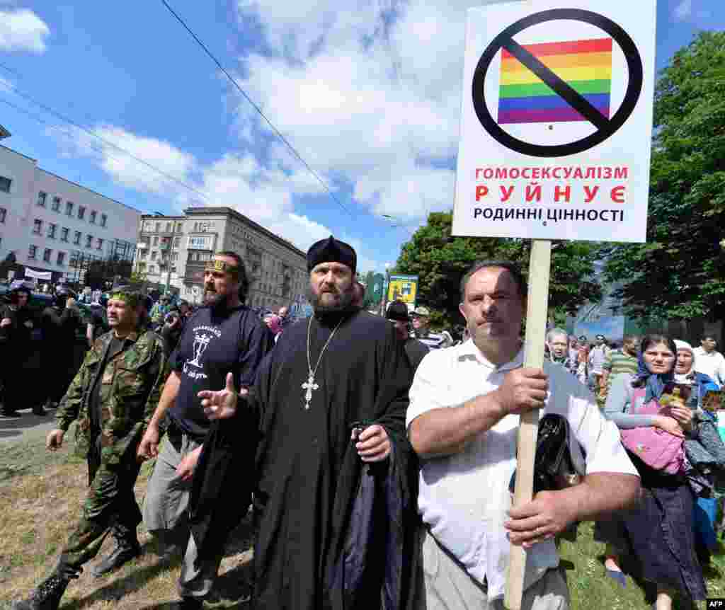 "Orthodox believers carry a placard saying ""Homosexuality destroys family values"" during a counterdemonstration."