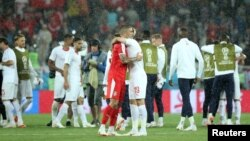 Serbia's Aleksandar Kolarov hugs Switzerland's Josip Drmic after their World Cup match.