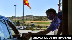 NORTH MACEDONIA -- Police officer takes documents from a motorist at the 'Bogorodica' border crossing between North Macedonia and Greece, near the southern city of Gevgelija, North Macedonia, 01 July.
