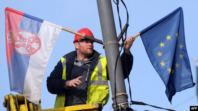 Serbia --  A worker arranges flags of Serbia and EU on a lamppost in Belgrade, 02Mar2012