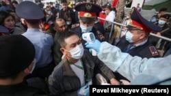 Медицинский работник измеряет температуру человеку на въезде в Алматы. 19 марта 2020 года.