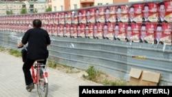 Велосипедист поминува покрај постери на владејачката партија за предвремените избори 2011.