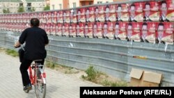 Велосипедист поминува покрај постери на владеачката партија за предвремените избори 2011