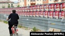 Велосипедист поминува покрај постери на владеачката партија за предвремените избори.