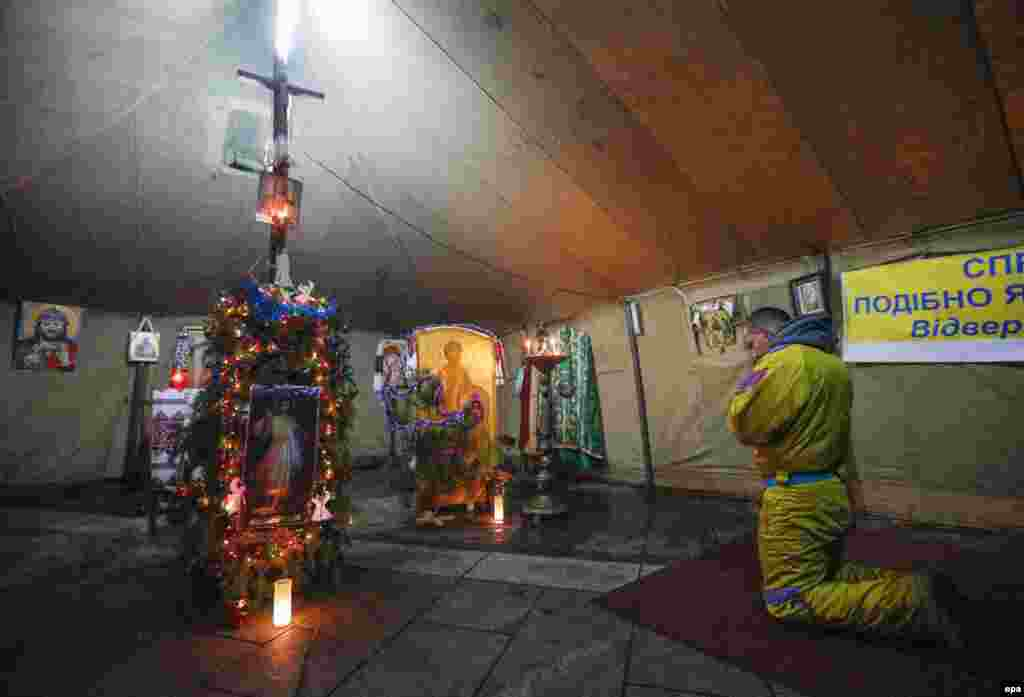 In Ukraine, a protester prays in an improvised church in a Ukrainian opposition camp tent on Independence Square in Kyiv on January 6, 2014.