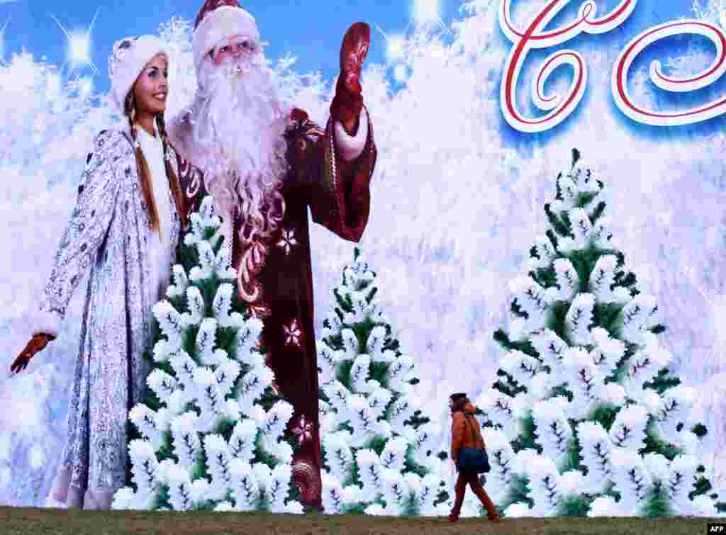 A man walks past a huge holiday Christmas and New Year's poster in Minsk. (AFP/Sergei Gapon)