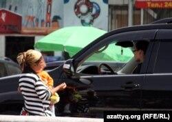 Женщина с ребенком просит деньги у проезжающих автомобилистов. Алматы.