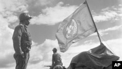 Doi soldați din cadrul Forțelor de Urgență ale Națiunilor Unite stau de pază la un avanpost din banda Gaza, între Egipt și Israel, 15 noiembrie 1957. UNEF, alcătuit din trupe din Brazilia, Canada, Columbia, Danemarca, Finlanda, India, Indonezia , Norvegia, Suedia și Iugoslavia, au păstrat pacea în regiune timp de un an.