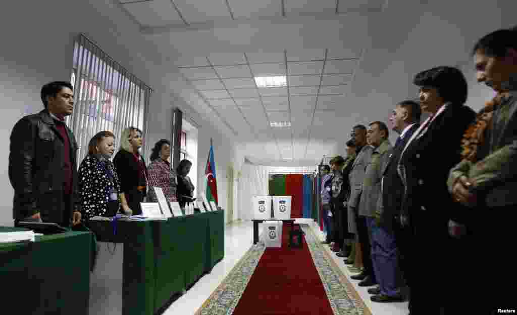 Election officials (left) and local observers listen to the national anthem as the polling station opens for voting in the presidential elections in Baku.