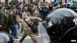 Мітингувальник кидає камінь у відділення «Сбербанку Росії», Київ, 20 лютого 2016 року