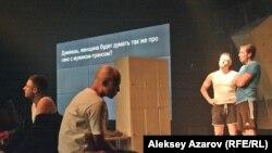 Сцена из спектакля «Тестостерон». Перевод речи актеров выводился в виде субтитров на монитор на стене. Алматы, 13 февраля 2018 года.