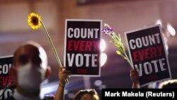 Активисти со цвеќиња и пароли по претседателските избори во САД во Филаделфија, Пенсилванија, 5 ноември 2020 година.