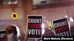 """Aktivisták virágokat, és """"Számoljanak össze minden szavazatot!"""" feliratú táblákat tartanak egy szavazóhelység közelében, ahol még tart a voksok összesítése Philadelphia városában, Pennsylvania államban, 2020. november 5-én."""