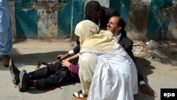 A doctor treats an injured lawyer at the scene of a suicide attack in the southwestern Pakistani city of Quetta. The August 8 attack killed 75 people. Most victims were lawyers.