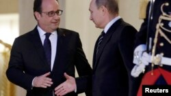 French President Francois Hollande (left) shakes hands with Russian President Vladimir Putin after a summit on the Ukraine crisis at the Elysee Palace in Paris on October 2.