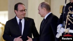 French President Francois Hollande (left) shakes hands with Russian President Vladimir Putin after a summit on the Ukraine crisis at the Elysee Palace in Paris, France, on October 2.
