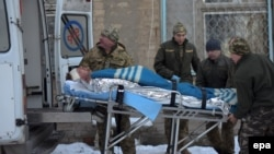 Members of a Ukrainian military medical unit carry an injured soldier from hospital to an ambulance as they prepare to evacuate from the eastern town of Avdiyivka on January 31.