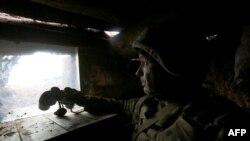 Украинский военный на позиции рядом с линией фронта, по ту сторону которой активизировались поддерживаемые Россией сепаратисты. Донбасс, 5 апреля 2021 года.