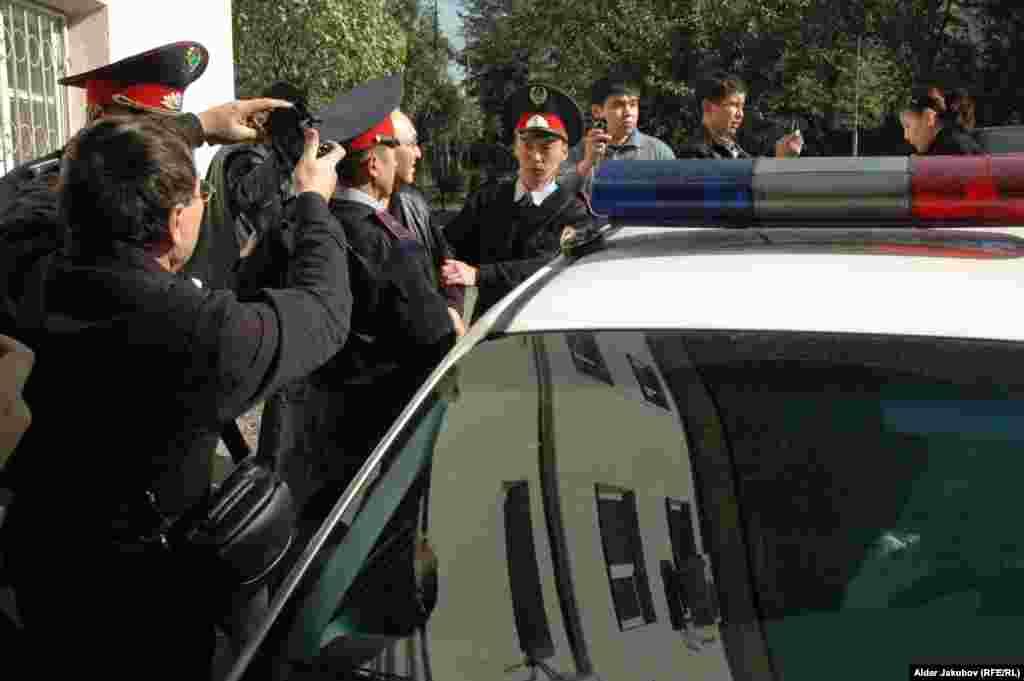 Шарипа Куракбаева прячут в полицейскую машину от агрессивной активистки - Полицейские садят Шарипа Куракбаева, журналиста оппозиционной газеты «Правда Казахстана», в полицейскую машину. Алматы, 27 октября 2010 года.